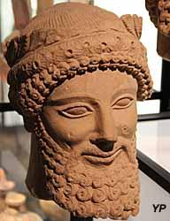 Musée de la Castre - tête barbue avec couronne de feuilles et de fleurs de narcisses en bouton, pierre calcaire (Chypre, 1ere moitié du 5e s. av. JC)