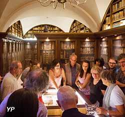 La bibliothécaire montrant un ouvrage de 1482 présentant la Cosmologie de Ptolémée (Médiathèque Protestante)