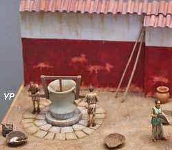 Atelier de meunier gallo-romain avec moulin à grains en pierre